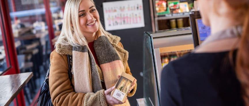 Kvinde i kiosk med sandwich