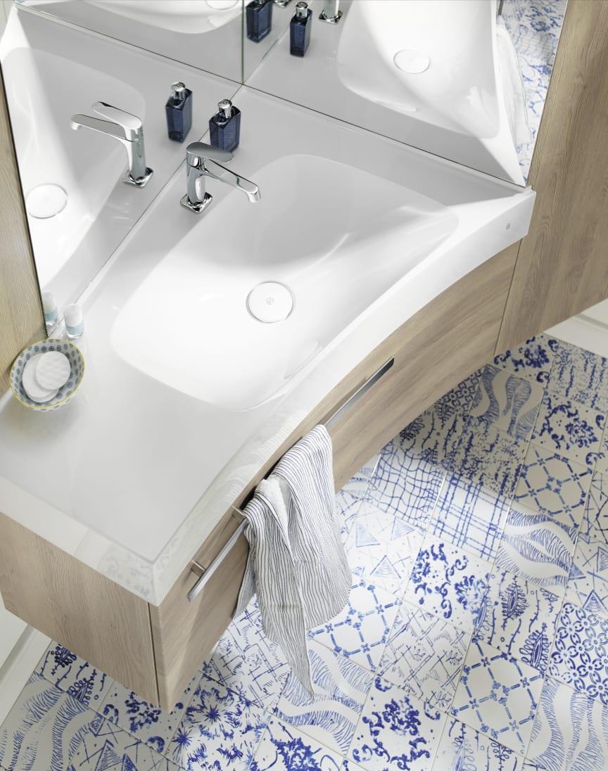 Sys30-Ecklösung von burgbad: Ein Möbel, das Waschtisch, Schränke, Spiegel und Beleuchtung zu einer kompakten Einheit zusammenfasst.
