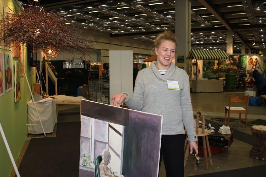 Felicia Kilander, hänger konstskolan Basis elevers konst i montern