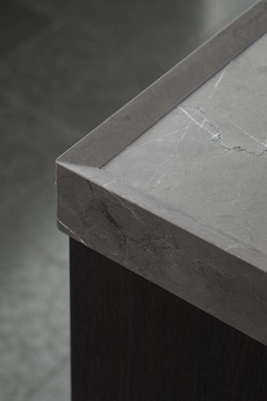 Marmorbordpladen har en skrå opkant, der giver en reliefagtig og let karakter til den kraftige bordplade - en af mange detaljer, som kendetegner den høje håndværksmæssige finish.