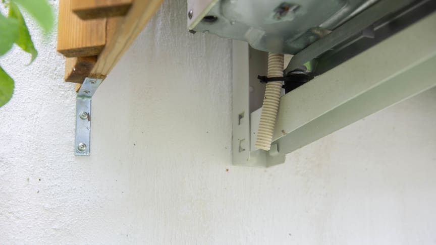 kondensvannslange på innsiden av varmepumpehus