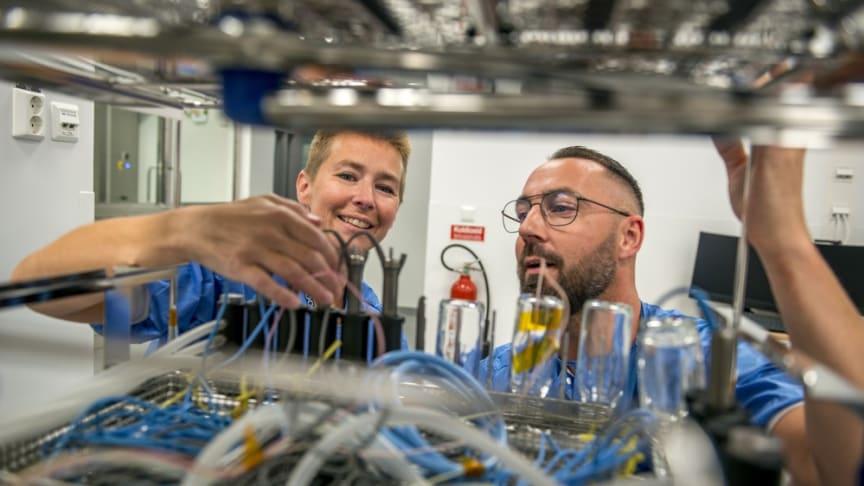 Sara Meurling och Andreas Bolin tittar in i diskdesinfektor