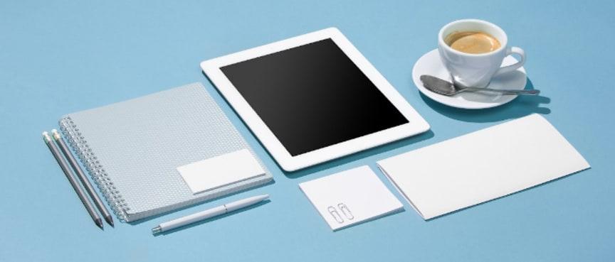Tablet, blok, penne og en kop kaffe