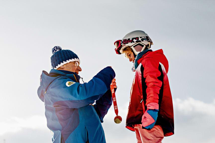 Skischulleiter Noldi Heinz überreicht einem Skischüler eine Medaille, Arosa Skischule, Arosa-Lenzeheide (Graubünden)