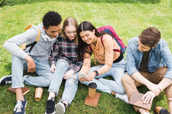En grupp av unga personer som sitter tillsammans i gräset och tittar på en mobiltelefon