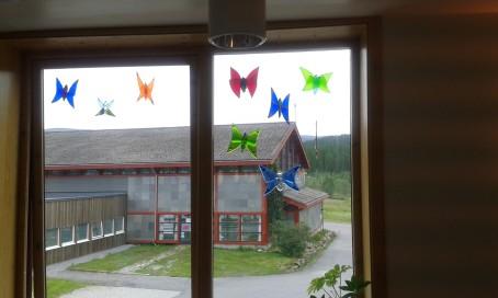 De fine fargene på sammerfuglene laget i glass kommer godt frem i vinduet .