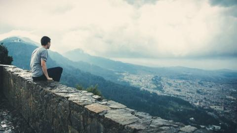 Man sitting on rock wall and overlooking city