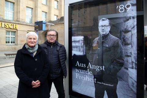 """Karin Wieckhorst und Uwe Frauendorf vor einem Plakat der Kampagne """"'89. Freiheit zur Veränderung. Menschen in Leipzig"""""""
