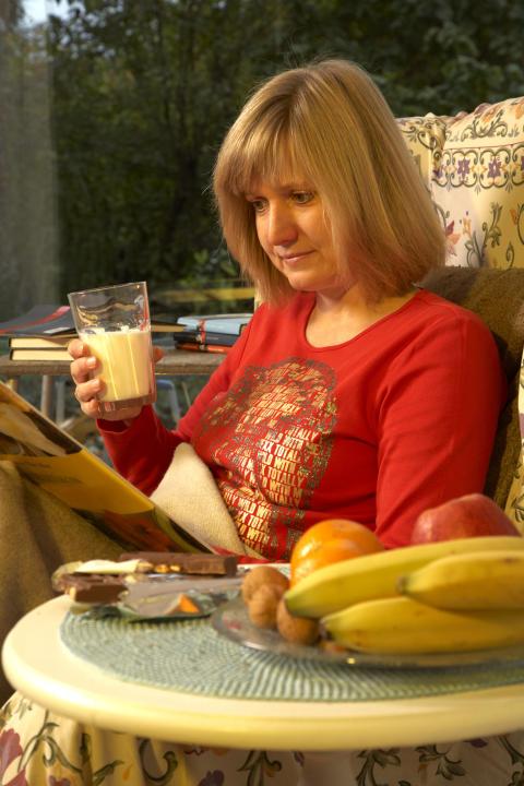 Frau liest im Sessel Hochformat