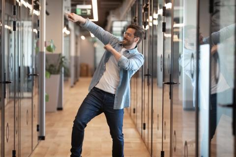 Mann som danser av glede fordi han har lyktes med å automatisere regnskapet.