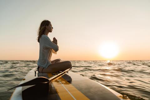 Junge Frau entschleunigt auf Paddleboard