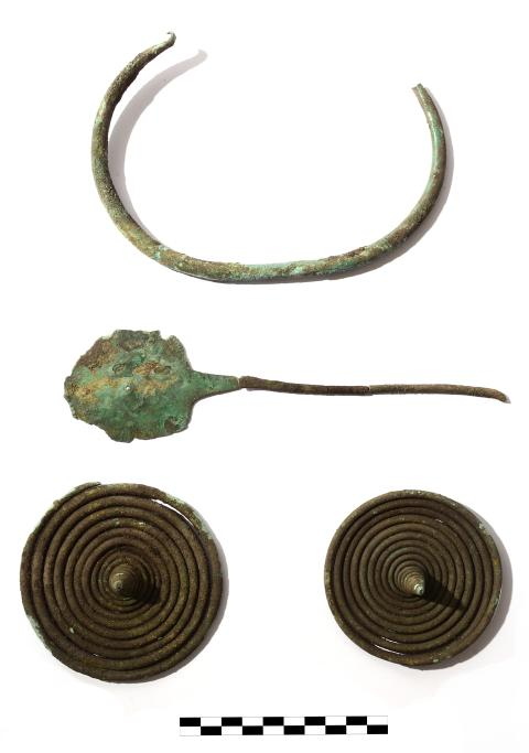 Eindeutige Fundstücke aus Bronze: Die beiden geborgenen Spiralen (unten), eine Fibel (Mitte) und ein Halsring gehören zu einer Frauentracht.