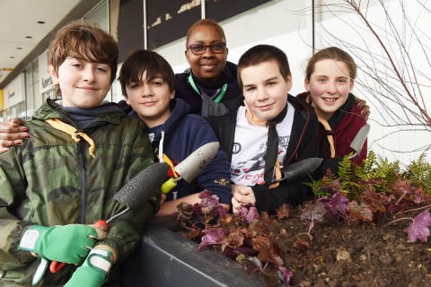 Great Linford Scout and railway staff fill new planters at Milton Keynes station
