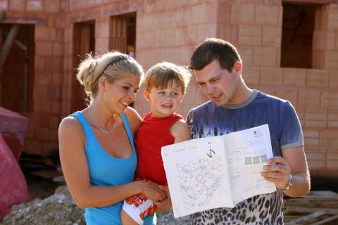 junge Familie vor Neubau im Sommer