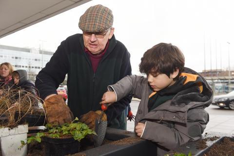 Milton Keynes Model Railway Society and local children fill planters at Milton Keynes station