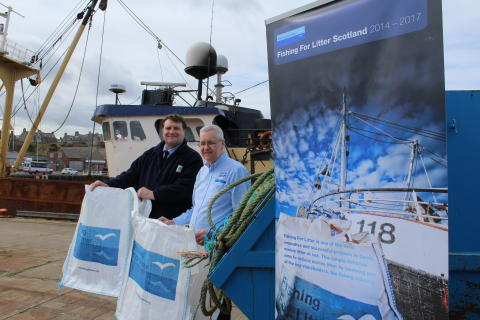 KIMO area coordinator, Graham Humphries and Buckie Harbour Master Clive Oxford with the free bags and skip at Buckie Harbour