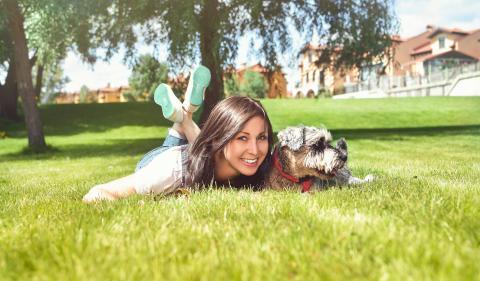 Frau mit Hund auf einer Wiese liegend