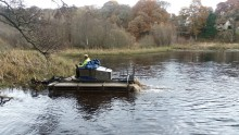 Amphibious weed-cutting machine helping to clear Sanquhar pond