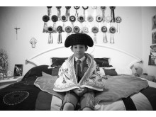 Salvador, aged 6, sits on his bed as he waits to depart for the afternoon bullfight, in Plaza Mexico