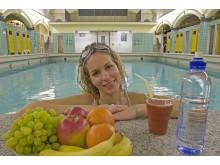 Frau mit Obstteller im Hallenbad