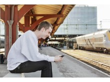 Resenär med mobil på perrongen
