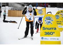 Alla på snö - barn åker skidor i bana