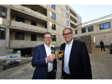 Dr. Bernd Hochberger (li.), Vorstandsmitglied der Stadtsparkasse München, stoßt zusammen mit dem Leiter des Immobilienmanagements, Michael Rubenbauer, auf das Richtfest des Neubaus in der Belgradstraße an.