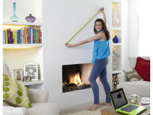 A woman struggling to guess how big a TV she could fit in her living room using a tape measure