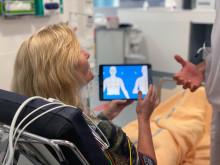 Patient som lyssnar på läkaren om hur man fyller i läsplattan CLEOS.