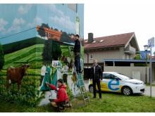 Heimatverbundenheit ziert Turmstation: Bayernwerk-Kommunalbetreuer Alexander Usselmann (rechts) besuchte die Art-EFX-Künstler Markus Ronge (links) und Pascal Sturm (Mitte) bei der Fertigstellung des Kunstwerks in Otterfing.