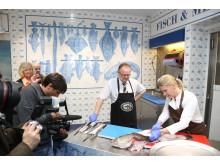 Fiskeriminister Per Sandberg og stjernekokken Cornelia Poletto viste hvordan man skal filetere en skrei.