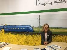 Maria Parent framför en bild på ett Pågatåg i Skåne. Ett exempel där Alstom har levererat regionaltåg till Sverige.