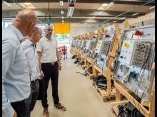 Carsten Sandby Knudsen, RITTAL A/S, t.v., Martin Nørgård Nielsen, RITTAL A/S, m.f., og Lars Farsø, FH Automation A/S, t.h., betragter en serie el-tavler under opbygning til en af de større vindmølleproducenter.
