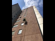 Reparbetare från Klätterservice utför fasadreparation.