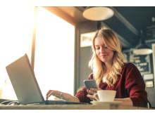 Ung kvinne på café som jobber på både mobil og laptop