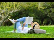 Frau liest auf einem Rasen liegend