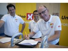 En svært fornøyd generalsekretær i NGTF, Øistein Leren, signerer kontrakten. I bakgrunn president i NGTF, Torgeir Pedersen, og Alex Guindos, daglig leder i Uno-X Forsyning