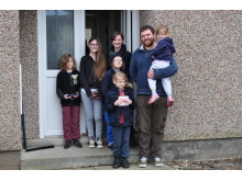 Alan and Claire Couper with family outside their new house