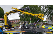 A moped that was seized by officers is removed