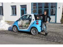 """Foto: Mit dem """"50 Jahre Jugend forscht E-Smart"""" trifft das Patenunternehmen Bayernwerk ehemalige bayerische Preisträger, hier Daniel Gurdan, und lässt diese das Elektroauto signieren."""
