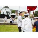 De første studenter på Tradium HTX hejser flaget foran skolen.