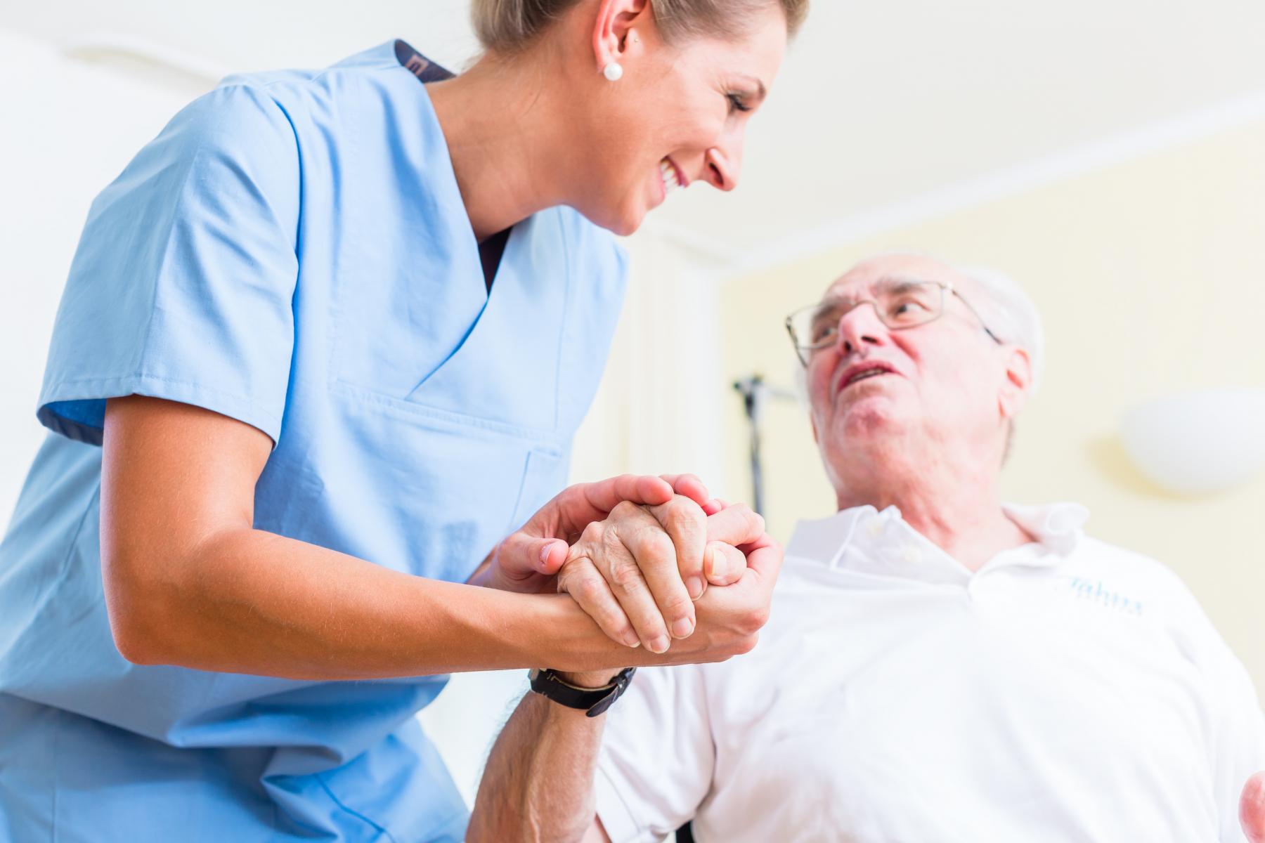 Sjuksköterska håller hand med patient.